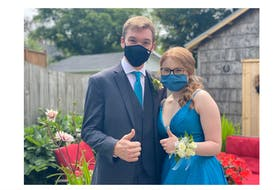 Yarmouth high school graduates Adam Box and Sarah Webber give a thumbs up while having prom photos taken on July 22. During these COVID times, proms had to be organized by parents and the community. TINA COMEAU