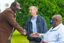 Progressive Conservative leader Tim Houston and Preston candidate Archy Beals shake hands with Marlowe Smith as they campaign in North Preston on Thursday, July 22, 2021.