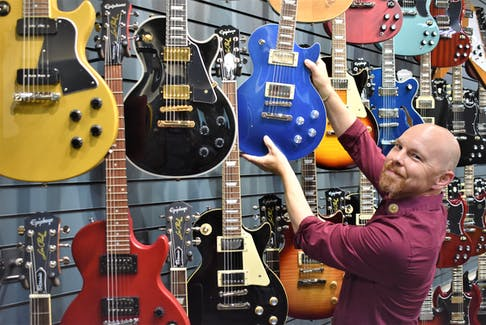 Truro's Long and McQuade Musical Instruments manager Tony Bouma by the large guitar display in the new store.