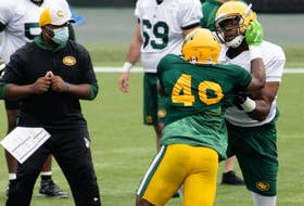 Thaddeus Coleman (50) and Shawn Lemon (40) go one-on-one during Edmonton Elks training camp at Commonwealth Stadium in Edmonton, on July 20, 2021. The team faces the Ottawa Redblacks in their first CFL game of the season at home on Aug. 7.