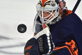 Edmonton Oilers goalie Mike Smith (41) makes a save against the Vancouver Canucks at Rogers Place in Edmonton on May 6, 2021.