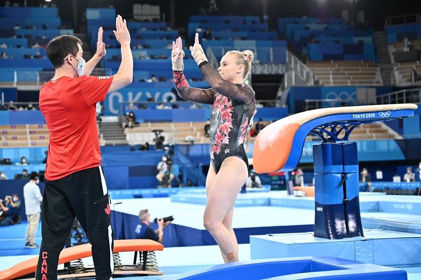 Halifax gymnast high-fives with coach David Kikuchi during team competition on Sunday at the Tokyo Olympics. - John Cheng/GymCan - Contributed