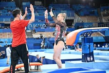 Halifax gymnast high-fives with coach David Kikuchi during team competition on Sunday at the Tokyo Olympics. - John Cheng/GymCan