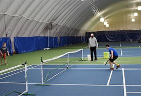 Using a temporary court marked by tape, summer camp attendees Carson Jones (left), Noah Carson, Ferris Rau and Noah Pollard try their hand at pickleball as Cougar Dome manager François Giguere looks on and provides a few pointers.