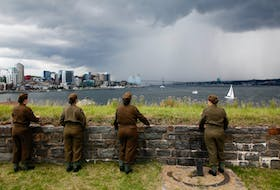 Tour guides with the Halifax Citadel Society dressed in Second World War military uniforms watch a rolling thunderstorm pass between Halifax and Dartmouth on Friday.  TIM KROCHAK PHOTO