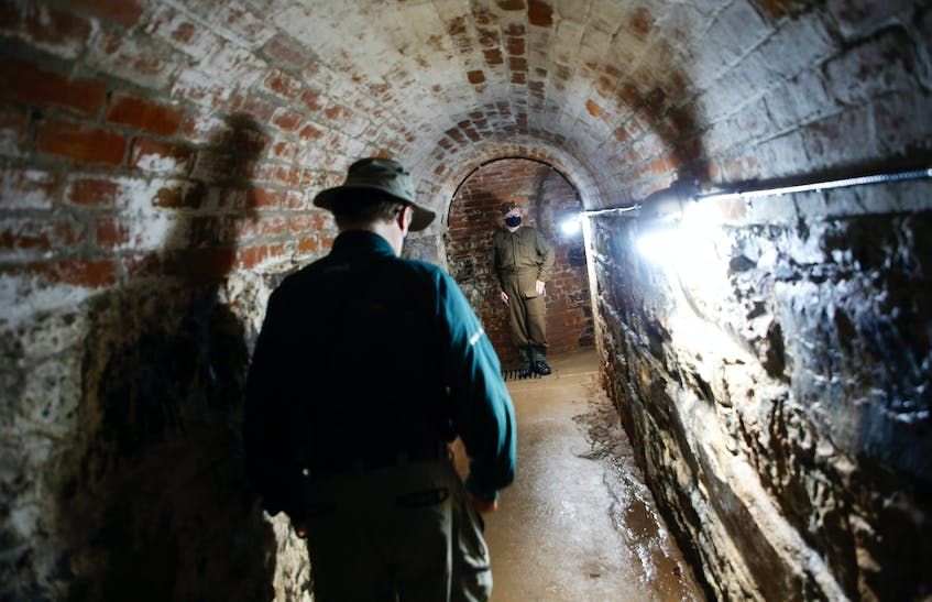 Hal Thompson with Parks Canada (left), and tour guide Gunner Bryce Walsh lead a tour of the tunnels under Fort Charlotte on Georges Island National Historic Site on Friday. - Tim Krochak