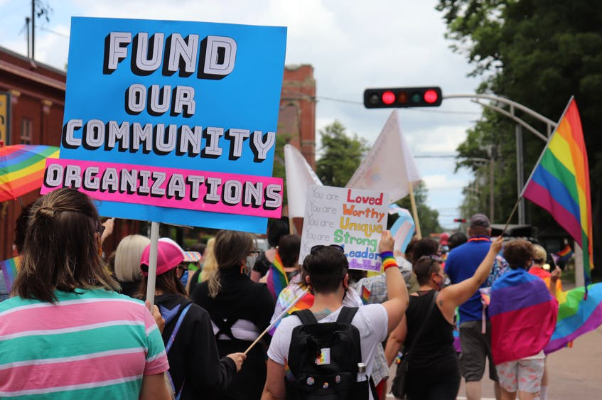 """While the queer community shares many of the same social and political issues, Pride march attendees also expressed their personal concerns through homemade signs like this one which says, """"Fund our community organizations"""". -  Logan MacLean"""