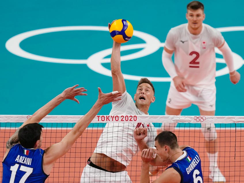 Canada's Lucas van Berkel spikes the ball past the Italian defence during their preliminary round pool A match between at the 2020 Summer Olympics, Saturday, July 24, 2021, in Tokyo, Japan. - Frank  Augstein