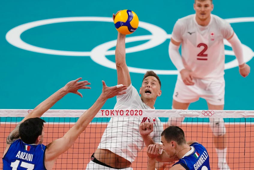 Canada's Lucas van Berkel spikes the ball past the Italian defence during their preliminary round pool A match between at the 2020 Summer Olympics, Saturday, July 24, 2021, in Tokyo, Japan.