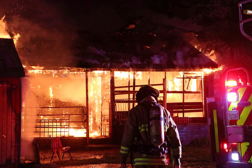 A firefighter is silhouetted by flames at a building in Upper Rawdon, Hants County, on Sunday night, July 25, 2021. - Adrian Johnstone