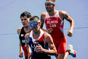 France's Vincent Luis (C), Japan's Kenji Nener (L) and Canada's Tyler Mislawchuk compete in the men's individual triathlon competition during the Tokyo 2020 Olympic Games at the Odaiba Marine Park in Tokyo on July 26, 2021.