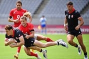 Canada's Phil Berna (L) is tackled by Britain's Tom Mitchell (C) in the men's pool B rugby sevens match between Britain and Canada during the Tokyo 2020 Olympic Games at the Tokyo Stadium in Tokyo on July 26, 2021. (Photo by Ben STANSALL / AFP)