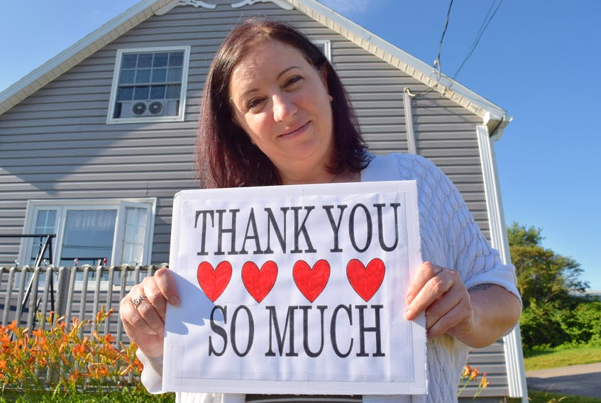 Shawna Wilson of Glace Bay stands in front of her home in Glace Bay with a message of gratitude to the public. A single mother only days away from their home going into foreclosure, she said the hearts of the public stepped up to help and they'll be forever grateful. Sharon Montgomery-Dupe/Cape Breton Post