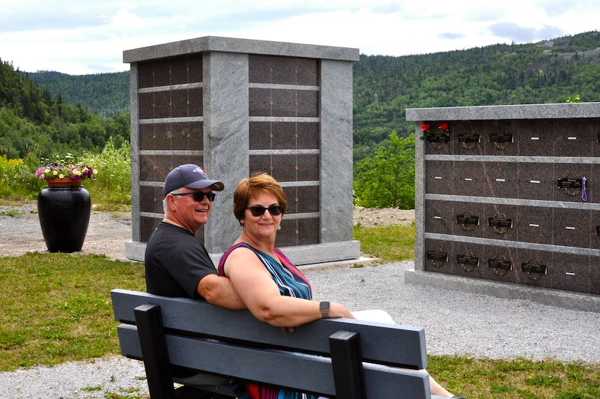 Dave and Sharon Higdon of Corner Brook sit on the bench in the columbarium park at Mount Patricia Cemetery  they purchased in memory of their parents. - Contributed