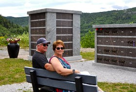 Dave and Sharon Higdon of Corner Brook sit on the bench in the columbarium park at Mount Patricia Cemetery  they purchased in memory of their parents.