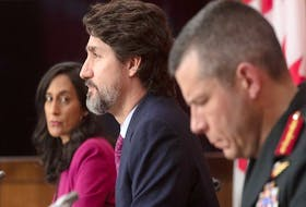 Public Services and Procurement Minister Anita Anand, left, and Maj.-Gen. Dany Fortin, right, look on as Prime Minister Justin Trudeau responds to a question during a news conference in Ottawa on Dec. 7, 2020.