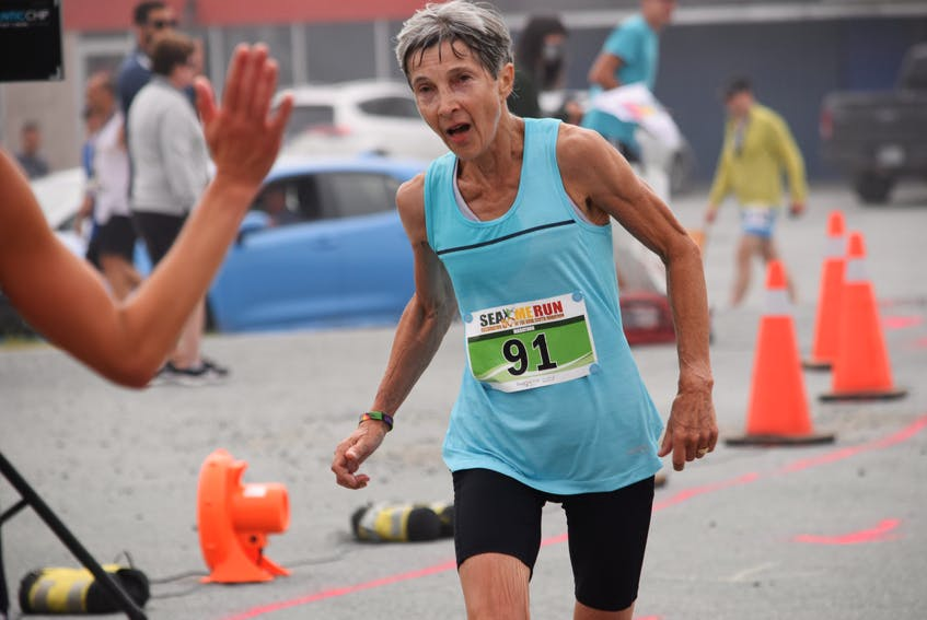 A high five awaits Halifax runner Morag McDonah at the finish line of the Nova Scotia Marathon on July 25. McDonah clocked a time of 3:21:38 to place first in the female 60-69 division. KATHY JOHNSON
