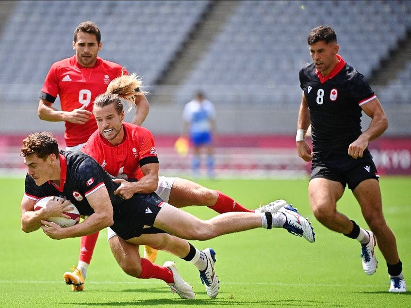 Canada's Phil Berna (left) is tackled by Britain's Tom Mitchell (centre) in the mens pool B rugby sevens match between Britain and Canada during the Tokyo 2020 Olympic Games at the Tokyo Stadium in Tokyo on July 26, 2021. - Postmedia  photo