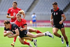 Canada's Phil Berna (left) is tackled by Britain's Tom Mitchell (centre) in the mens pool B rugby sevens match between Britain and Canada during the Tokyo 2020 Olympic Games at the Tokyo Stadium in Tokyo on July 26, 2021.