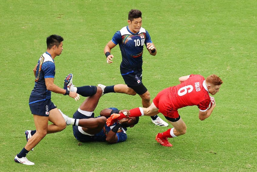 Connor Braid of Team Canada is tackled by Lote Tuqiri of Team Japan.