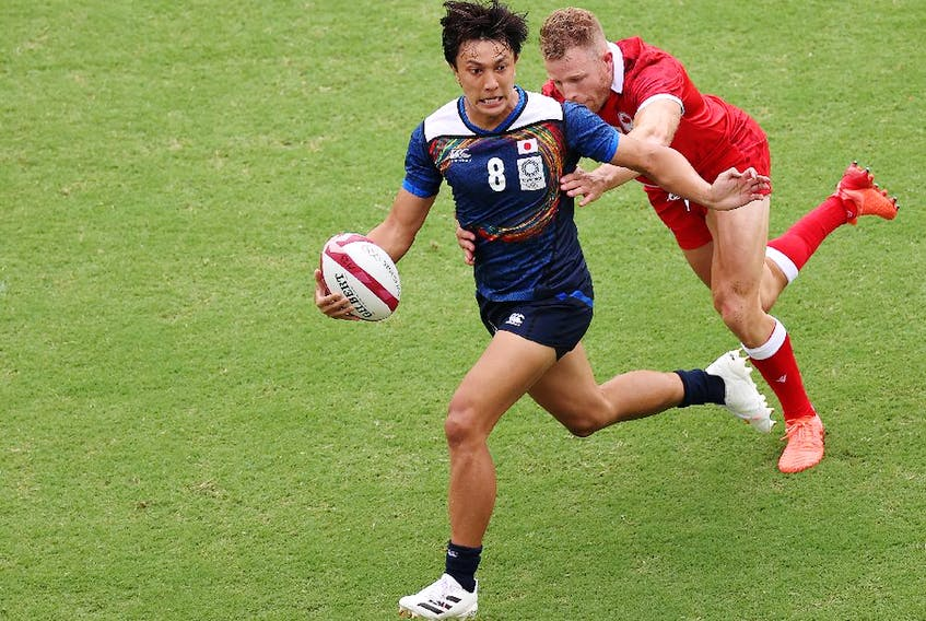 Chihito Matsui of Team Japan runs with the ball under pressure from Conor Trainor of Team Canada during the Men's Pool B Rugby Sevens match between Canada and Japan on day four of the Tokyo 2020 Olympic Games at Tokyo Stadium on July 27, 2021 in Chofu, Tokyo, Japan.