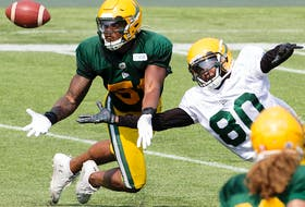 Nyles Morgan (51) and Armanti Edwards (80) battle for the ball during Edmonton Elks training camp at Commonwealth Stadium on Tuesday, July 27, 2021.