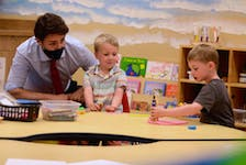 Prime Minister Justin Trudeau watches Mattéo, centre, and Henry play with some Play-Doh and toys July 27 at the Carrefour de l'Isle-Saint-Jean in Charlottetown. The prime minister was in town for a joint federal-provincial government announcement that will see an average of $10 a day early learning and child care in P.E.I. in three years.