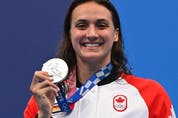 Canada's Kylie Masse poses with her medal on the podium after the final of the women's 100m backstroke swimming event during the Tokyo 2020 Olympic Games at the Tokyo Aquatics Centre in Tokyo on July 27, 2021.