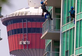 Window washers clean the glass on the Arriva tower in Calgary's Victoria Park area on Monday, July 26, 2021.