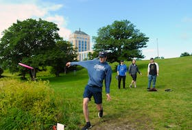 Cameron Hickman tees off at St. John's first disc golf tournament last weekend, as (from left to right) Kris Moulton, Riley Brooks and Mike Fardy look on.