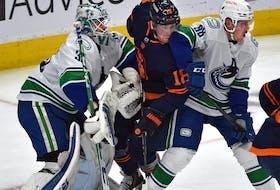 Edmonton Oilers James Neal (18) gets sandwich between Vancouver Canucks Nate Schmidt (88) and goalie Thatcher Demko (35) at Rogers Place in Edmonton, May 6, 2021.