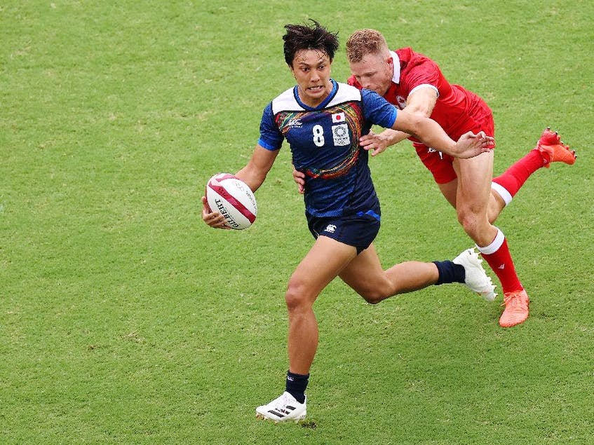 Chihito Matsui of Team Japan runs with the ball under pressure from Conor Trainor of Team Canada during the Men's Pool B Rugby Sevens match between Canada and Japan on day four of the Tokyo 2020 Olympic Games at Tokyo Stadium on July 27, 2021 in Chofu, Tokyo, Japan. - Postmedia  photo