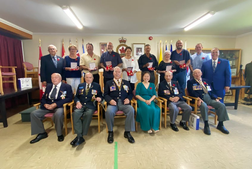 Korean War veterans, family members of veterans – including deceased veterans – and other invited guests pose for a photo following a ceremony at the Wedgeport Legion on July 24. TINA COMEAU