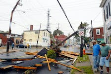 Passersby look at the debris on Agricola Street in September 2003 after hurricane Juan uprooted trees and downed power lines throughout the region.