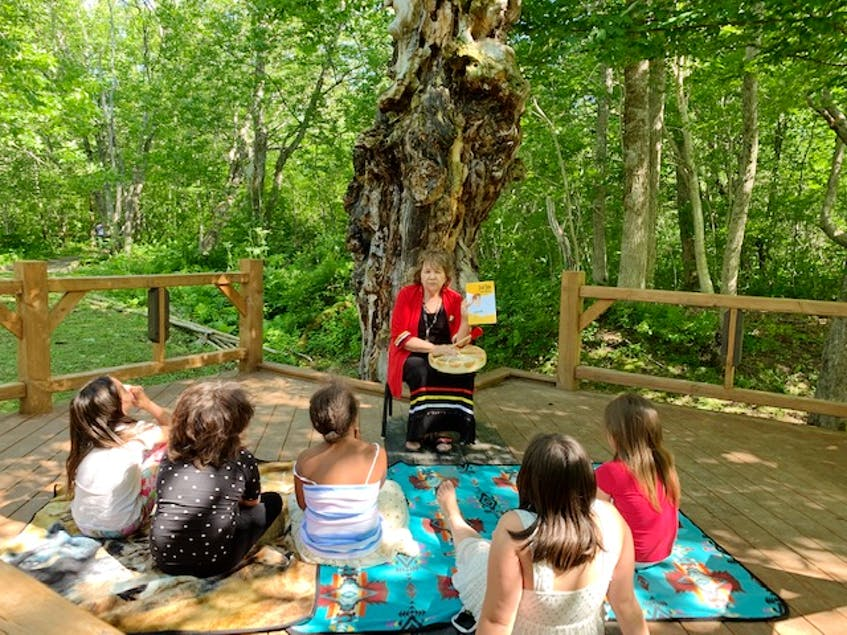 Elder Phylis Googoo reads books to children in Mi'kmaw and English around The Tree of a Thousand Faces as part of a cultural event in 2020. CONTRIBUTED