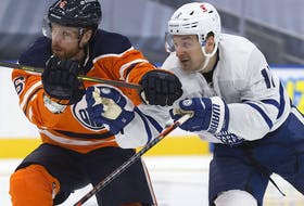 The Edmonton Oilers defence man Adam Larsson (6) battles the Toronto Maple Leafs' Zach Hyman (11) at Rogers Place in Edmonton on Feb. 27, 2021.