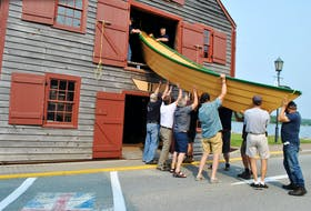 A wooden dory is lowered down from the building loft in the Shelburne Dory Shop Museum during the vessel's launch on July 21 on historic Dock Street in Shelburne. KATHY JOHNSON