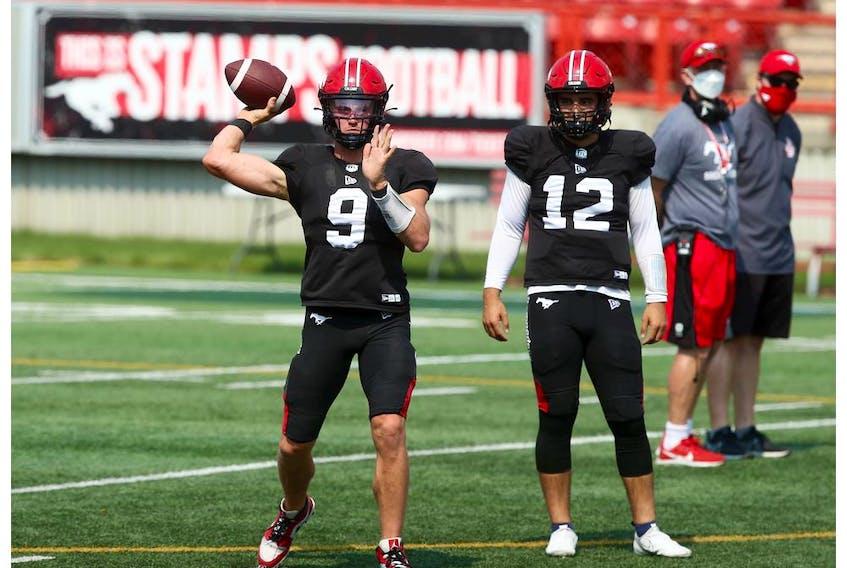 Dakota Prukop throws as fellow quarterback Jake Maier  looks on during Calgary Stampeders training camp at McMahon Stadium in Calgary on Saturday, July 24, 2021.