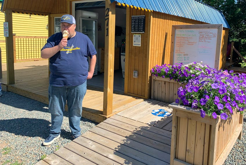 Daniel Curren tucks into a cone of candy cane ice cream outside his Tatamagouche Ice Creamery shop, which is doing a thriving business on the village's main street.