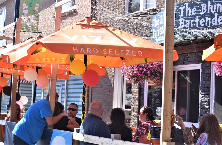 Dave Connors (standing) from the Blunt Bartender greets customers enjoying the patio on a warm Saturday afternoon. - Richard MacKenzie