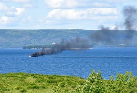 """A small boat caught on fire and sank near Cape Breton's St. George's Channel on Thursday, July 29. Ken Thorneycroft took this photo from his deck at Leonard's Pond about two kilometres east of the Dundee Resort. """"I was first alerted to it by a Coast Guard DASH-8 flying overhead,"""" Thorneycroft told the Cape Breton Post. """"From my deck I was able to see rescue boats departing the burning wreak. I do not believe anyone was injured or left on board. The wreak was left to float away and subsequently left my field of view."""" No further information is available at this time. CONTRIBUTED/KEN THORNEYCROFT"""