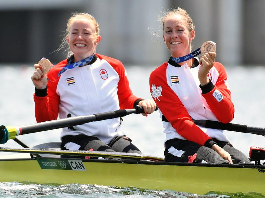 Bronze medallists Caileigh Filmer of Canada and Hillary Janssens of Canada celebrate with their medals in their boat. - PIROSCHKA  VAN DE WOUW