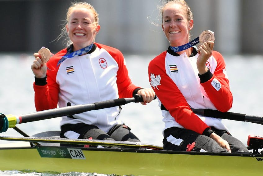 Bronze medallists Caileigh Filmer of Canada and Hillary Janssens of Canada celebrate with their medals in their boat.