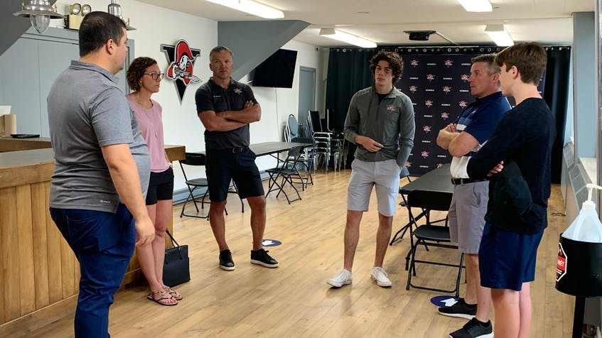 Tyler Peddle, centre, and his family meet with Drummondville Voltigeurs head coach Steve Hartley, left, and general manager Philippe Boucher at the QMJHL team's facility earlier this summer.