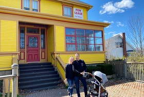 Colette O'Hara, Ezra Edelstein and their son in front of The August House.