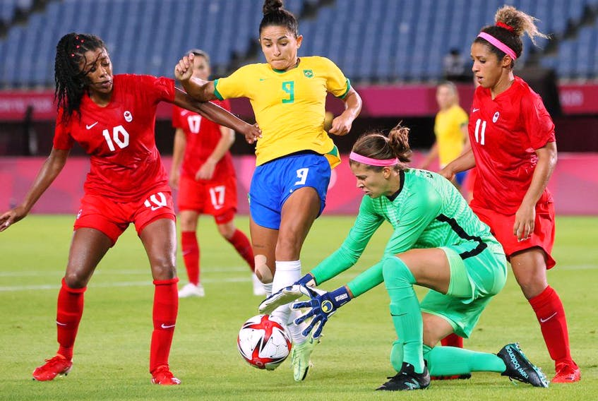 Stephanie Labbe #1 of Team Canada collects the ball whilst under pressure from Debinha #9 of Team Brazil during the Women's Quarter Final match between Canada and Brazil on day seven of the Tokyo 2020 Olympic Games at Miyagi Stadium on July 30, 2021 in Rifu, Miyagi, Japan.