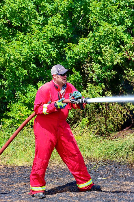 Captain Jeremy Walsh worked to hit hot spots along a tree line to prevent the fire from spreading. - Adrian Johnstone