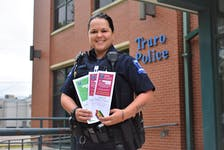 """Cst. Amanda Assoun holds up the three different Positive Tickets Truro Police Services will be handing out. """"I think it's a great way to interact with the public on a positive note,"""" she said."""