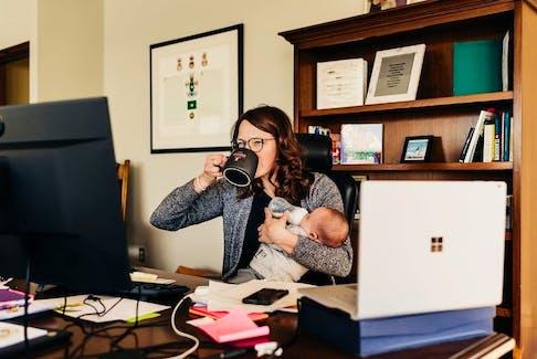 Cape Breton Mayor Amanda McDougall and baby Emmett both grab a drink in her office in Cape Breton Regional Municipality.
