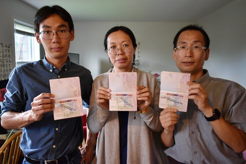 """Edward Wang, left, his mom, Julie Zhu, and his dad, Jerry Wang, stand in their small, two-bedroom apartment in Charlottetown, holding their passports stamped """"Cancelled Without Prejudice""""."""